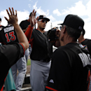 Miami Marlins right fielder Giancarlo Stanton is congratulated by teammates after making a diving catch on a ball hit by St. Louis Cardinals' Allen Craig to end the first inning of an exhibition spring training baseball game Friday, Feb. 28, 2014, in Jupi