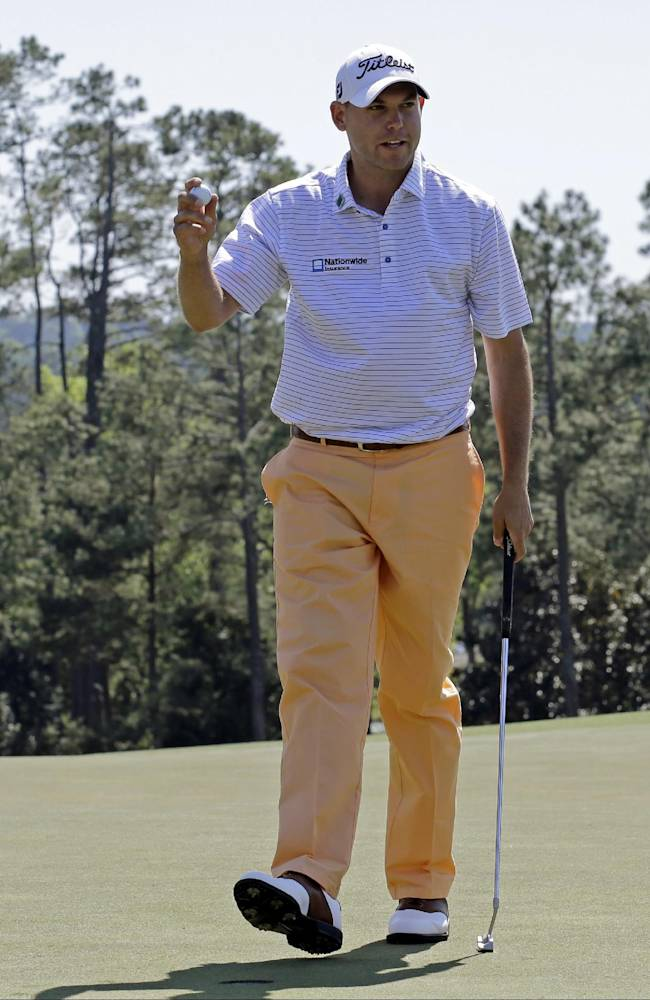 Bill Haas holds up his ball after a birdie putt on the 18th hole during the first round of the Masters golf tournament Thursday, April 10, 2014, in Augusta, Ga