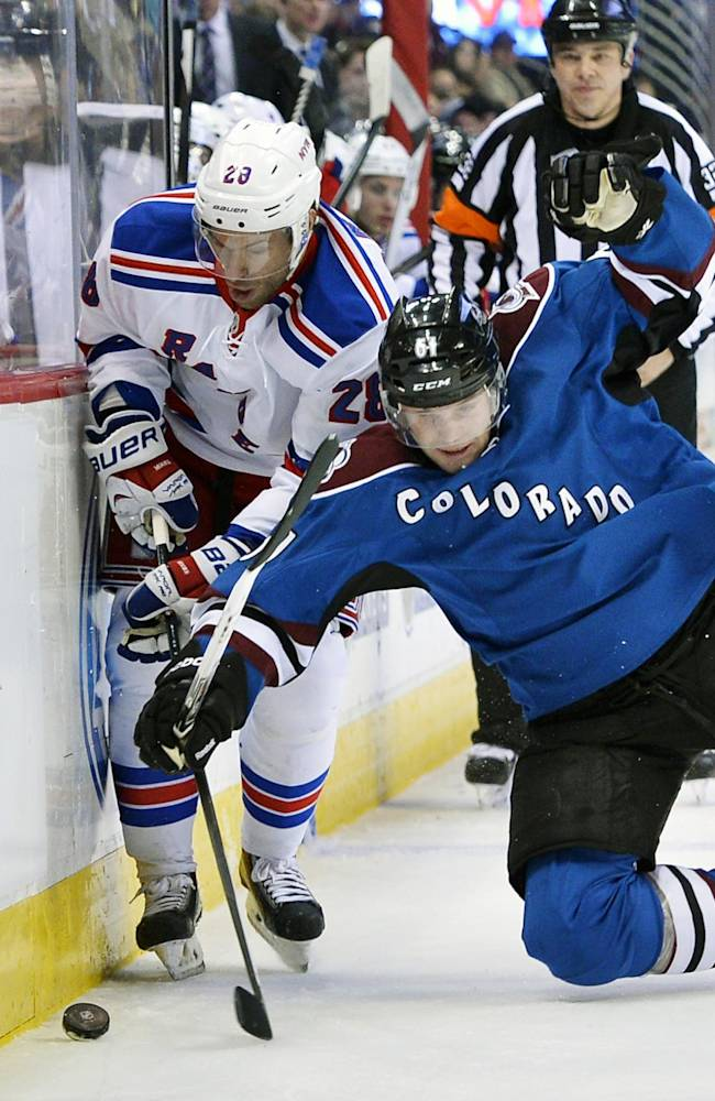 Colorado Avalanche defenseman Andre Benoit (61) dives to control the puck against New York Rangers' Dominic Moore (28) during the second period of an NHL hockey game on Thursday, April 3, 2014, in Denver