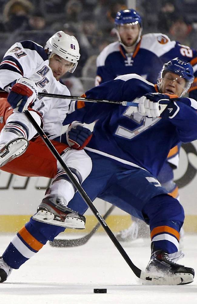 New York Islanders right wing Kyle Okposo (21) checks New York Rangers left wing Rick Nash (61) during the second period of an outdoor NHL hockey game at Yankee Stadium in New York, Wednesday, Jan. 29, 2014