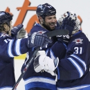 Winnipeg Jets' Olli Jokinen (12), Zach Bogosian (44) and goaltender Ondrej Pavelec (31) celebrate a win over the Phoenix Coyotes in a shootout in NHL hockey game action in Winnipeg, Manitoba, Thursday, Feb. 27, 2014 The Associated Press