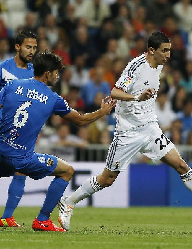 Real's Angel Di Maria, right, in action with Almeria's Marcos Tebar, centre, during a Spanish La Liga soccer match between Real Madrid and Almeria at the Santiago Bernabeu  stadium in Madrid, Spain, Saturday, April 12, 2014