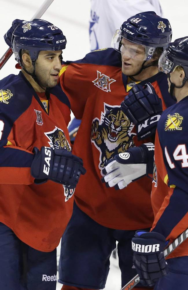 Florida Panthers center Scott Gomez (23) is congratulated by Jonathan Huberdeau, center, and Tomas Fleischmann (14) after scoring a goal in the second period during a preseason NHL hockey game against the Tampa Bay Lightning, Saturday, Sept. 28, 2013, in Sunrise, Fla
