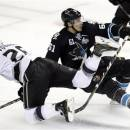 San Jose Sharks' Justin Braun (61) collides with Los Angeles Kings defenseman Slava Voynov (26), of Russia, during the third period in Game 4 of their second-round NHL hockey Stanley Cup playoff series in San Jose, Calif., Tuesday, May 21, 2013. San Jose won 2-1.(AP Photo/Marcio Jose Sanchez)