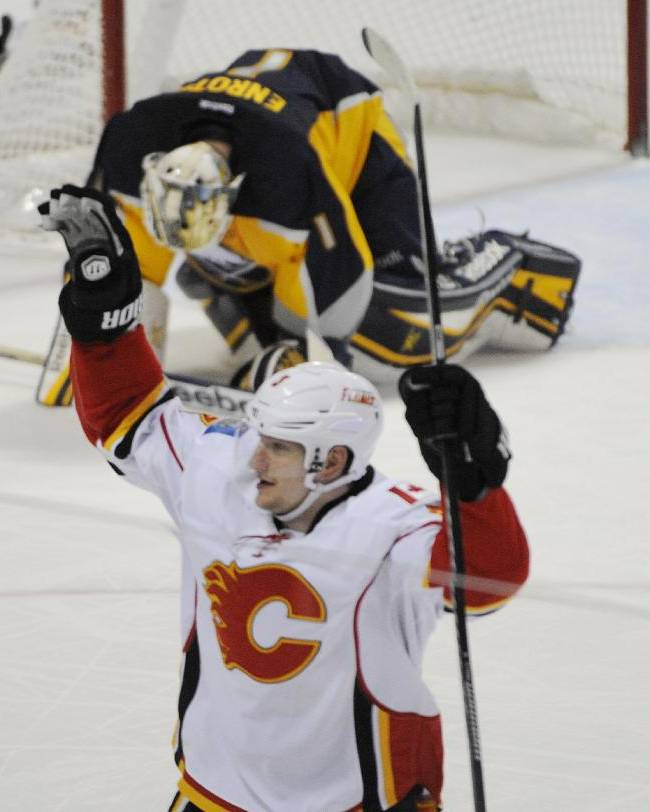 Calgary Flames defenseman Ladislav Smid, of the Czech Republic, celebrates a game winning goal by Matt Stajan, as Buffalo Sabres goaltender Jhonas Enroth, of Sweden, reacts during the overtime session of an NHL hockey game in Buffalo, N.Y., Saturday Dec. 14, 2013. Calgary won 2-1