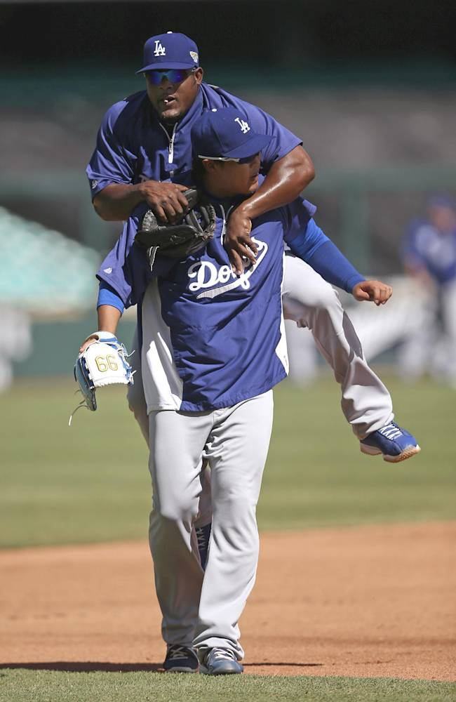 Los Angeles Dodgers' Juan Uribe, back, jumps onto teammate Hyun-Jin Ryu as their team trains at the Sydney Cricket Ground in Sydney, Friday, March 21, 2014. Major League Baseball will open their season Saturday in Sydney with the Dodgers taking on the Arizona Diamondbacks