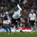 Fulham's Dimitar Berbatov, right, is tackled by Aston Villa's Fabian Delph during their English Premier League soccer match at Craven Cottage, London, Sunday, Dec. 8, 2013