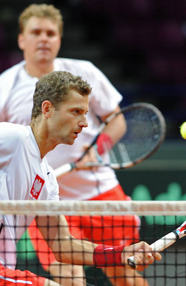 Poland's Mariusz Fyrstenberg, front, returns a ball as Marcin Matkowski looks on during their Davis Cup playoff round doubles tennis match against Australia's Chris Guccione and Nick Kyrgios in Warsaw, Poland, Saturday, Sept. 14, 2013