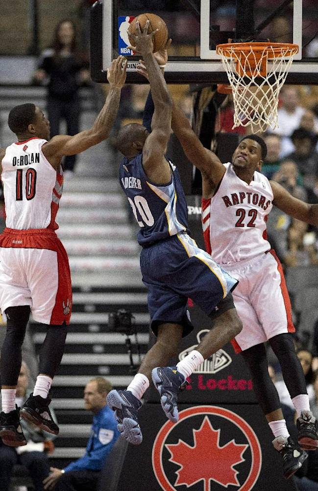 Memphis Grizzlies' Quincy Pondexter, center, tries to shoot with Toronto Raptors' DeMar DeRozan (10) and Rudy Gay (22) defending during the first half of a preseason NBA basketball game in Toronto on Wednesday, Oct. 23, 2013