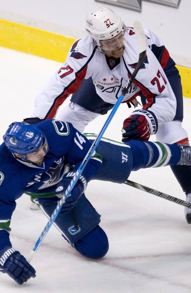 Vancouver Canucks forward Alex Burrows (14) fights for control of the puck with Washington Capitals defenceman Karl Alzner (27) during the second period of NHL hockey action in Vancouver, British Columbia on Monday, Oct. 28, 2013