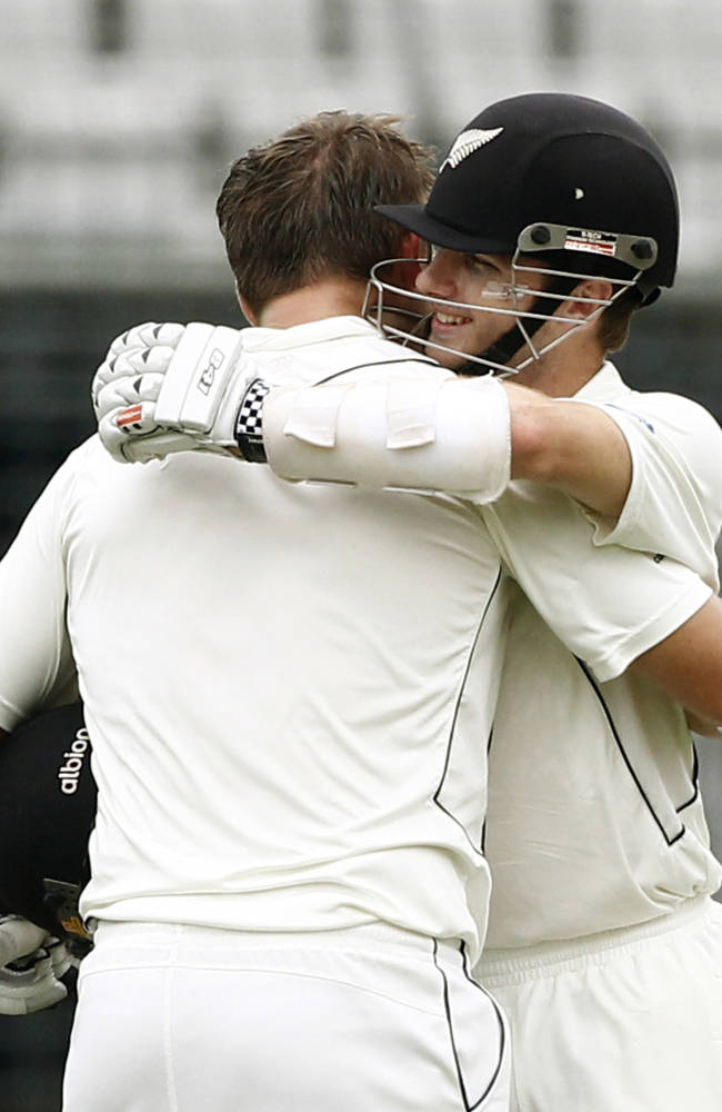 New Zealand's Kane Williamson, right, congratulates teammate Corey Anderson for scoring a century on the third day of the second cricket test match against Bangladesh in Dhaka, Bangladesh, Wednesday, Oct. 23, 2013