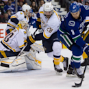 Vancouver Canucks' Zack Kassian, right, attempts a shot against Nashville Predators goalie Carter Hutton, left, as Paul Gaustad defends during first-period NHL hockey game action in Vancouver, British Columbia, Wednesday, March 19, 2014 The Associated Pre
