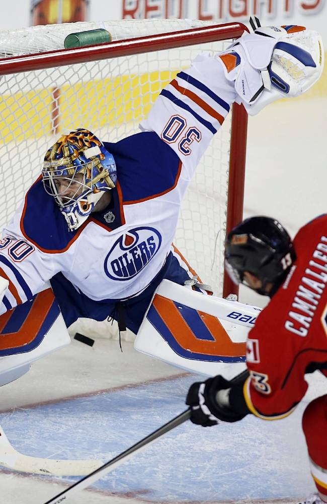 Edmonton Oilers' goalie Richard Bachman, left, lets in a goal from Calgary Flames' Mike Cammalleri during third-period NHL preseason hockey game action in Calgary, Alberta, Saturday, Sept. 14, 2013. The Oilers won 3-2