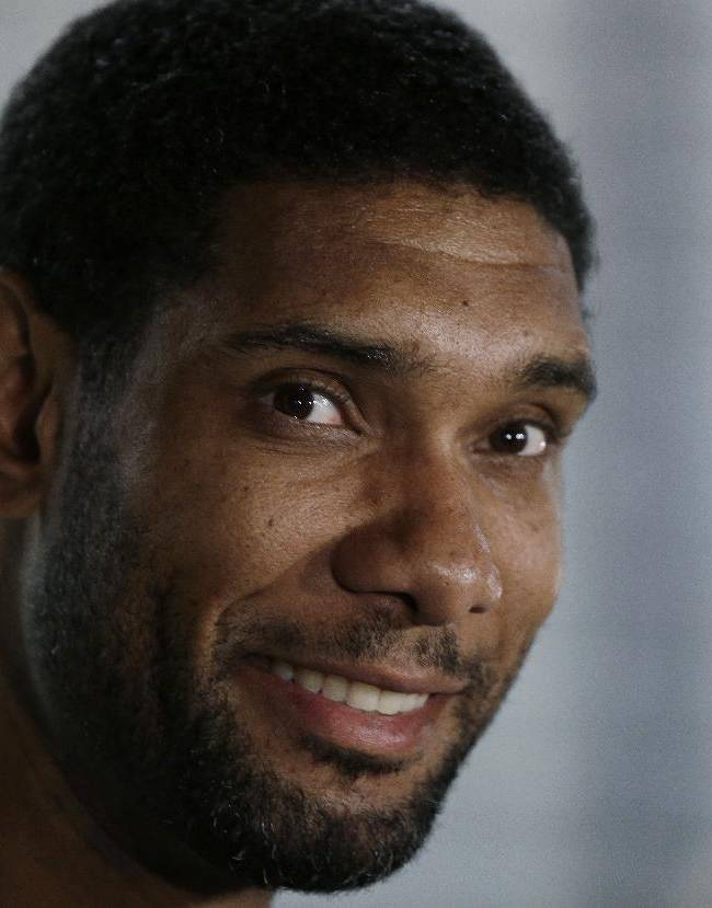 San Antonio Spurs' Tim Duncan, center, talks to reporters at the team's workout facility during their NBA basketball media day, Monday, Sept. 30, 2013, in San Antonio
