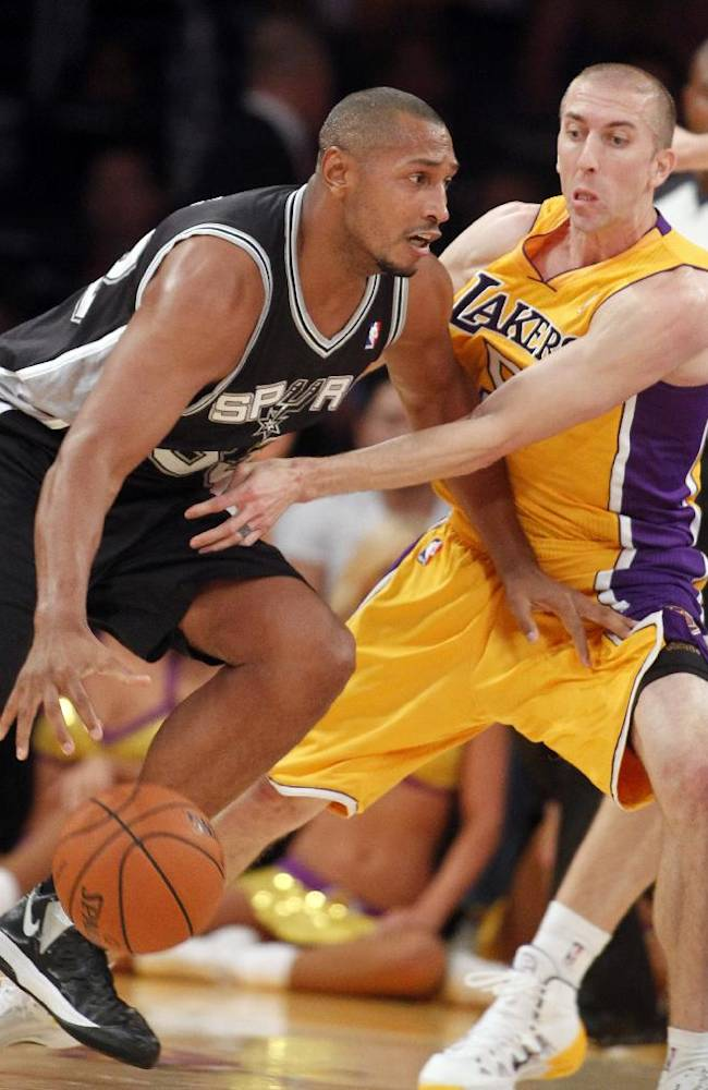 San Antonio Spurs forward Boris Diaw, left, of France, drives with the ball against Los Angeles Lakers guard Steve Blake during the second quarter of an NBA basketball game Friday, Nov. 1, 2013, in Los Angeles