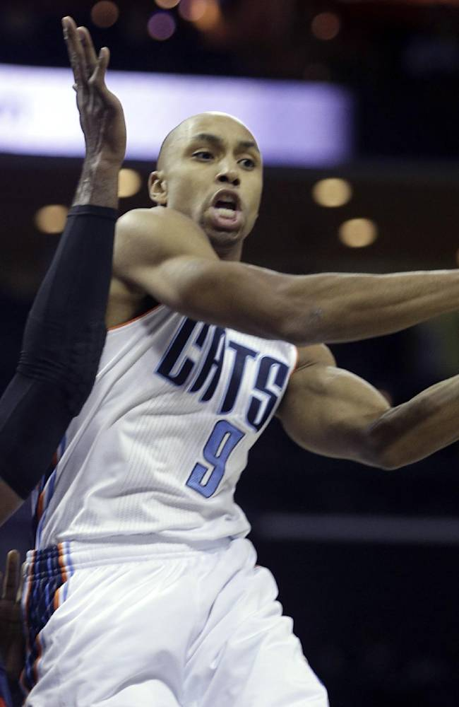 Charlotte Bobcats guard Gerald Henderson, right, passes around Atlanta Hawks forward Paul Millsap in the first half of an NBA basketball game in Charlotte, N.C., Monday, Nov. 11, 2013