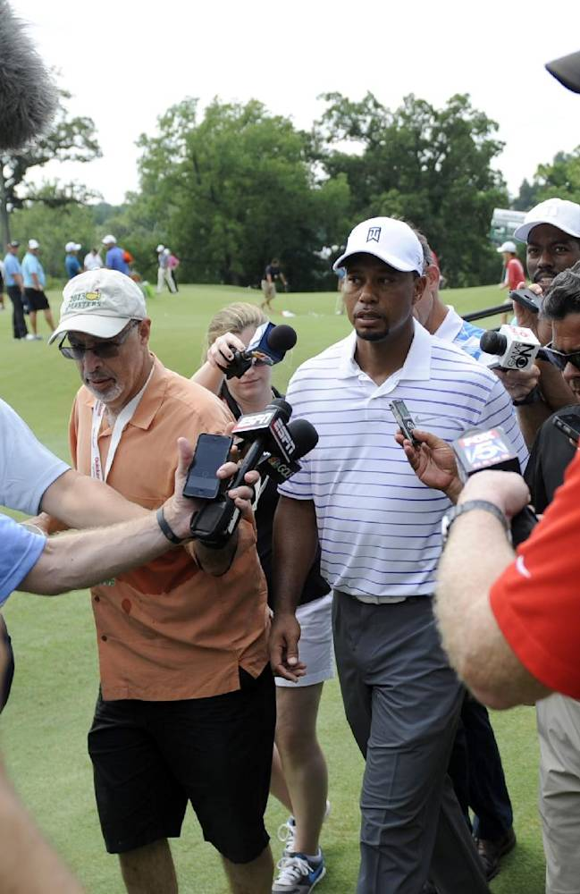 Tiger Woods is mobbed by the media after his round in the Pro-Am at the Quicken Loans National golf tournament, Wednesday, June 25, 2014, in Bethesda, Md
