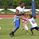 Buffalo Bills running back Fred Jackson (22) plays with his children following a practice at their NFL football training camp in Pittsford, N.Y., Monday, July 21, 2014. With him are daughters Jaeden and Kaelen and son, Braeden (L-R) The Associated Press