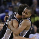 San Antonio Spurs' Patty Mills, right, hugs Marco Belinelli at the end of an NBA basketball game against the Golden State Warriors, Thursday, Dec. 19, 2013, in Oakland, Calif. San Antonio won 104-102.(AP Photo/Ben Margot)