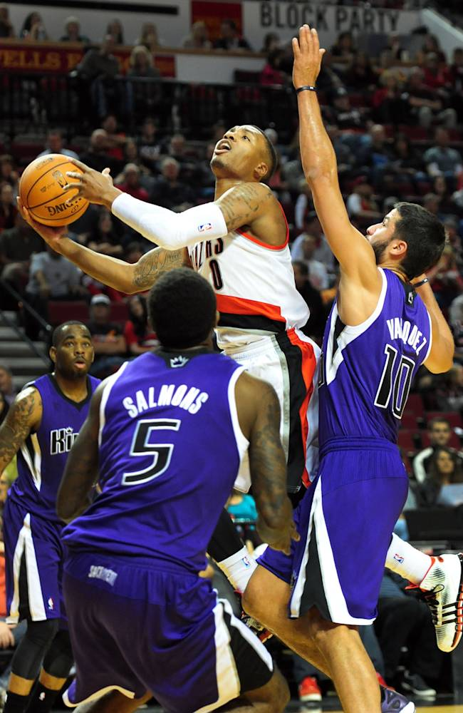 Portland Trail Blazers guard Damian Lillard (0) drives to the basket on Sacramento Kings guard Greivis Vasquez (10) during the first half of an NBA basketball game Sunday, Oct. 20, 2013, in Milwaukee