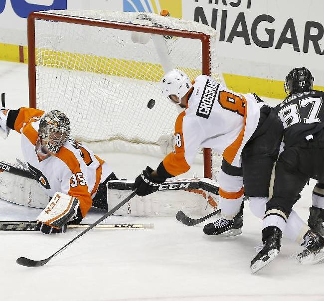 Philadelphia Flyers goalie Steve Mason (35) looks back as a shot by Pittsburgh Penguins' Sidney Crosby (87) bounces off the post behind Nicklas Grossmann (8), of Sweden, during the third period of an NHL hockey game on Sunday, March 16, 2014, in Pittsburgh. The Flyers won 4-3