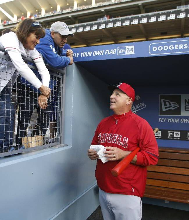 Los Angeles Angels manager Mike Scioscia talks to someone in the stands before the Angels' exhibition baseball game against the Los Angeles Dodgers in Los Angeles, Friday, March 28, 2014