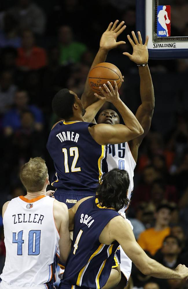 Indiana Pacers forward Evan Turner (12) shoots over Charlotte Bobcats center Bismack Biyombo as Charlotte Bobcats center Cody Zeller (40) and Indiana Pacers forward Luis Scola look on during the first half of an NBA basketball game in Charlotte, N.C., Wednesday, March 5, 2014