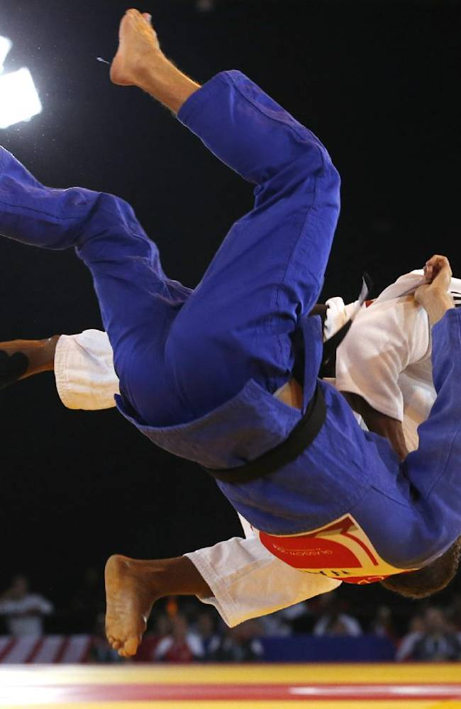 Siyabulela Mabulu of South Africa, in white, throws Jamie Macdonald of Wales during their men's 66kg judo preliminary round bout at the Commonwealth Games Glasgow 2014, in Glasgow, Scotland Thursday, July, 24, 2014
