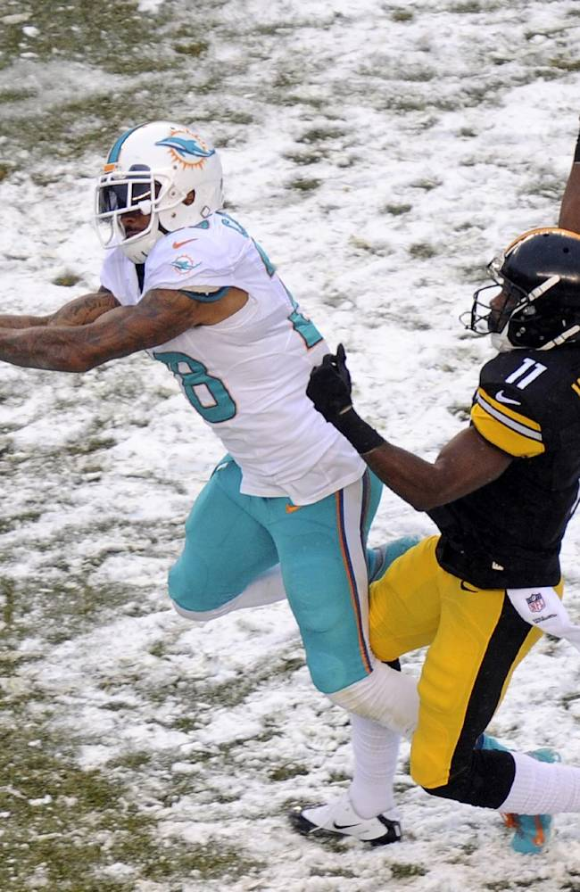 Miami Dolphins cornerback Nolan Carroll (28) cannot come up with the interception of a pass intended for Pittsburgh Steelers wide receiver Markus Wheaton (11) during the second half of an NFL football game in Pittsburgh, Sunday, Dec. 8, 2013