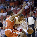 Miami Heat guard Mario Chalmers, right, drives around Milwaukee Bucks guard Brandon Knight (11) during the first half of an NBA basketball game on Wednesday, April 2, 2014, in Miami The Associated Press