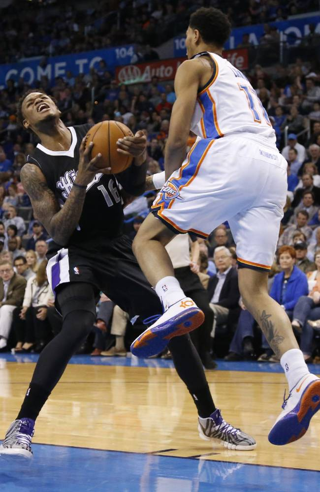 Sacramento Kings guard Ben McLemore (16) is fouled by Oklahoma City Thunder guard Jeremy Lamb (11) during the first quarter of an NBA basketball game in Oklahoma City, Friday, March 28, 2014