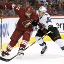 San Jose Sharks' Justin Braun (61) slaps the puck away from Arizona Coyotes' Brandon McMillan (22) during the second period of an NHL hockey game Tuesday, Jan. 13, 2015, in Glendale, Ariz. The Sharks won 3-2 The Associated Press