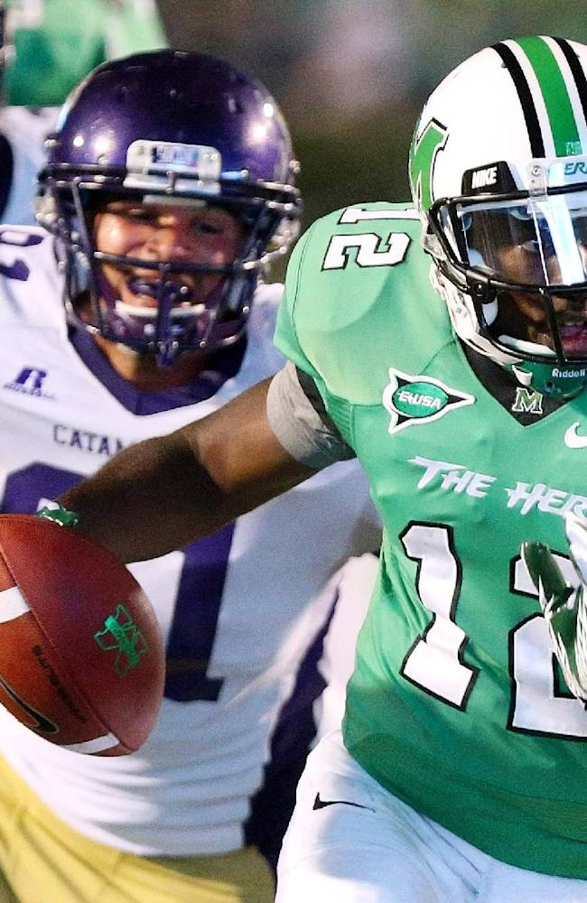 In this Sept. 8, 2012, file photo, Marshall's Rakeem Cato runs a quarterback keeper as Western Carolina defender Brian Johnson chases him during an NCAA college football game in Huntington, W.Va. Cato enters his senior season with the chance to become the most prolific quarterback in school history