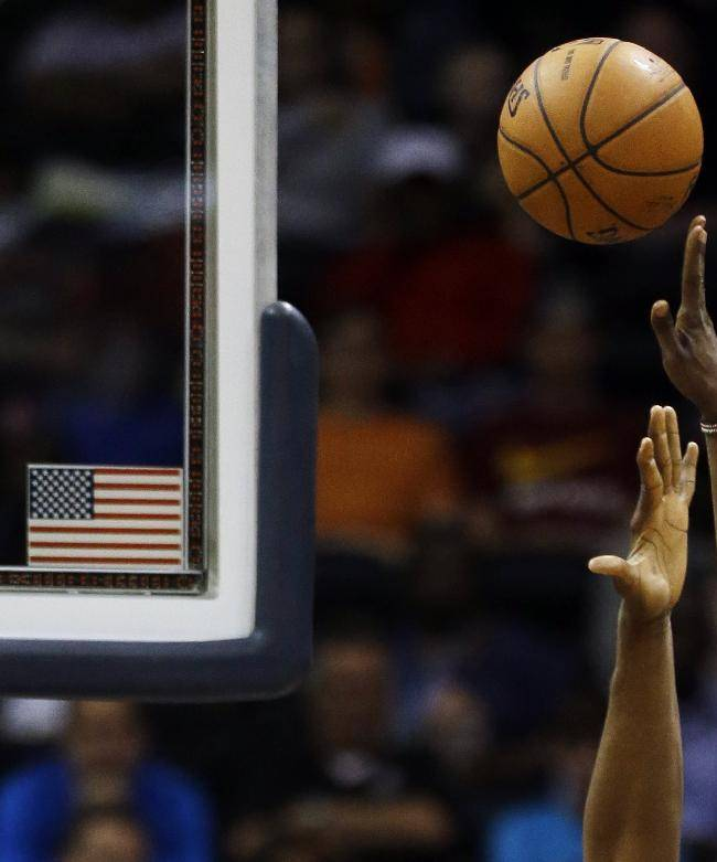 The arm of Cleveland Cavaliers' Luol Deng, of Sudan, right, shoots the ball over the reach of Atlanta Hawks' Elton Brand in the first quarter of an NBA basketball game, Friday, April 4, 2014, in Atlanta