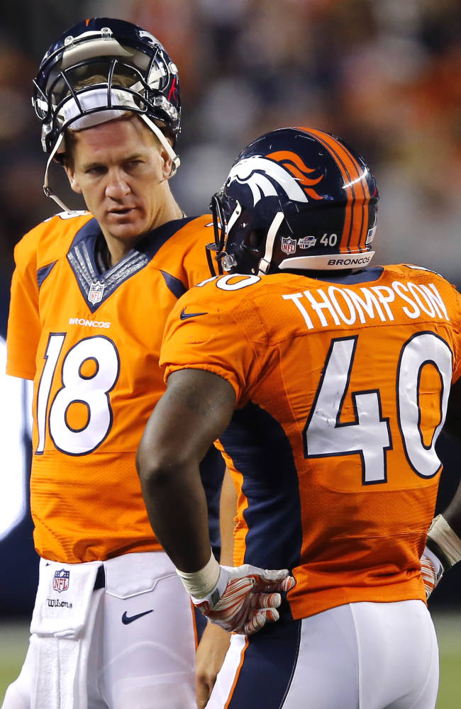 Denver Broncos quarterback Peyton Manning (18) talks with with Juwan Thompson (40) during the second half of an NFL preseason football game against the Houston Texans, Saturday, Aug. 23, 2014, in Denver