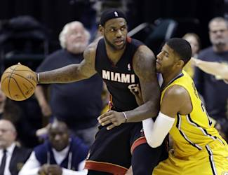 Miami Heat forward LeBron James, left, is defended by Indiana Pacers forward Paul George in the second half of an NBA basketball game in Indianapolis, Tuesday, Dec. 10, 2013. The Pacers won 90-84. (AP Photo/Michael Conroy)