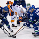 New York Islanders' Kyle Okposo (21) and Thomas Hickey (14) battle for the puck with Vancouver Canucks' Luca Sbisa (5), of Switzerland; (5) and Henrik Sedin, of Sweden, in front of goalie Eddie Lack, of Sweden, during the third period of an NHL hockey gam
