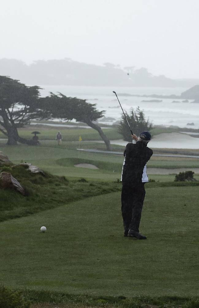 Charles Schwab hits from the 11th tee of the Monterey Peninsula Country Club Shore Course as George Roberts, right, looks on during the first round of the AT&T Pebble Beach Pro-Am golf tournament Thursday, Feb. 6, 2014, in Pebble Beach, Calif. Play was suspended because of steady rain. Schwab is the founder of the Charles Schwab Corporation