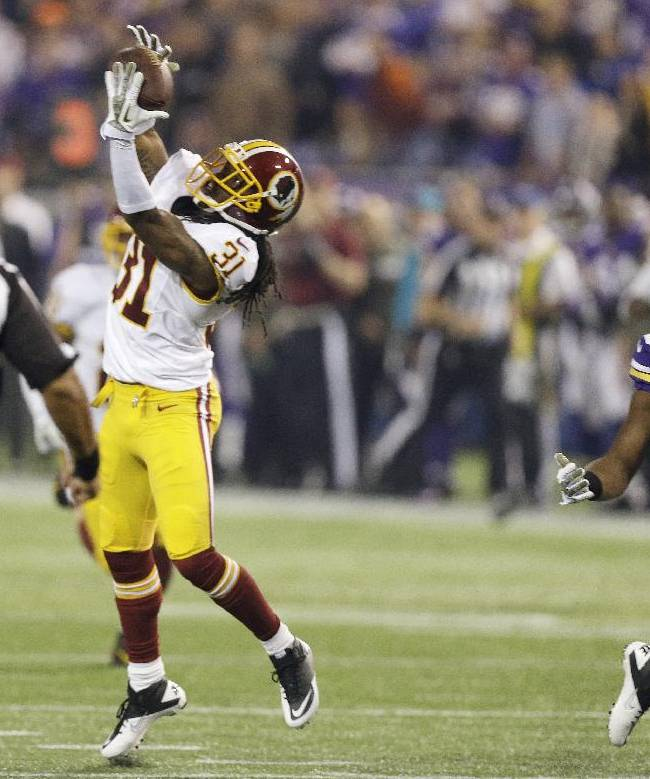 Washington Redskins strong safety Brandon Meriweather, left, intercepts a pass intended for Minnesota Vikings wide receiver Greg Jennings during the first half of an NFL football game, Thursday, Nov. 7, 2013, in Minneapolis