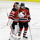 New Jersey Devils' Peter Harrold (10) congratulates goalie Cory Schneider (35) after defeating the Toronto Maple Leafs 3-2 in an NHL hockey game Sunday, March 23, 2014, in Newark, N.J The Associated Press