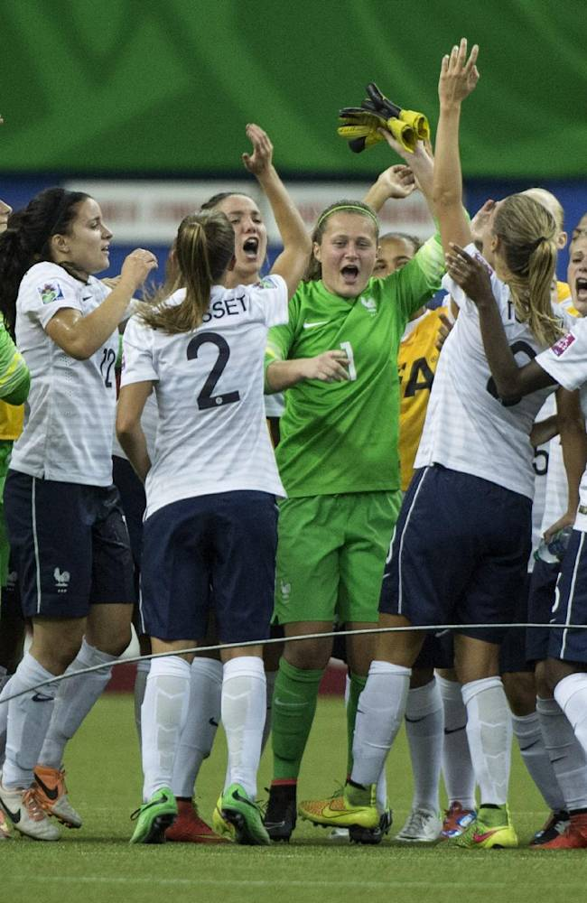 France goalkeeper Romane Bruneau (1) is surrounded by teammates to celebrate their 3-2 victory over North Korea in the FIFA U20 Women's World Cup match for third place in Montreal on Sunday, Aug. 24, 2014