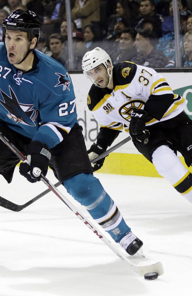 San Jose Sharks' Scott Hannan (27) is chased by Boston Bruins' Patrice Bergeron (37) during the second period of an NHL hockey game on Saturday, Jan. 11, 2014, in San Jose, Calif