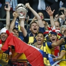Arsenal's Per Mertesacker, centre, holds the trophy after the English FA Cup final soccer match between Aston Villa and Arsenal at Wembley stadium in London, Saturday, May 30, 2015. Arsenal won the match 4-0. (AP Photo/Alastair Grant)