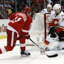 Detroit Red Wings' Daniel Alfredsson (11) takes a shot against Calgary Flames' T.J. Brodie (7) during the second period of an NHL hockey game Thursday, Dec. 19, 2013, in Detroit. (AP Photo/Duane Burleson)