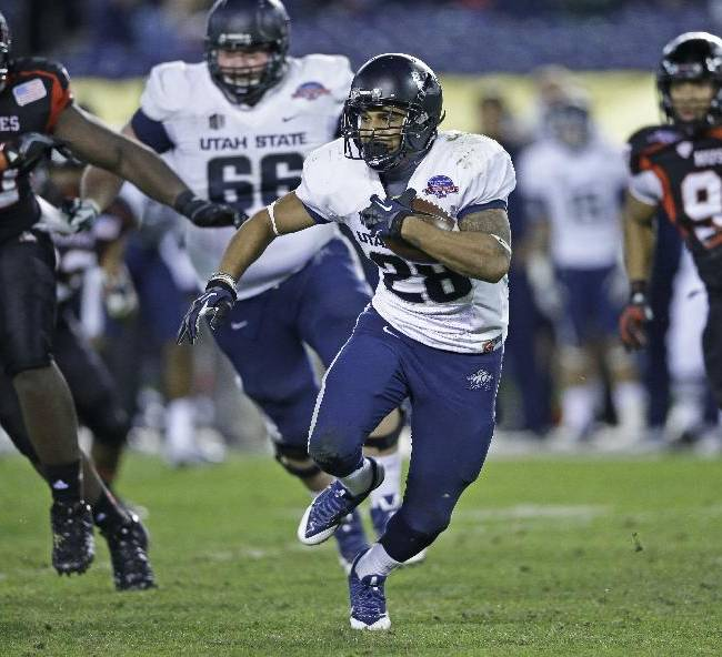 Utah State running back Joey DeMartino breaks through the Northern Illinois defense while gaining part of his 143 yards rushing during Utah State's 21-14 victory in the Poinsettia Bowl NCAA college football game, Thursday, Dec. 26, 2013, in San Diego. DeMartino was named the offensive player of the game