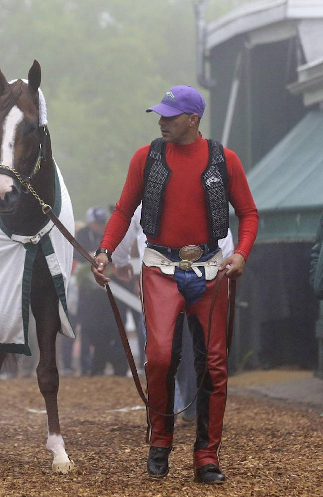 Exercise rider Willie Delgado, center, leads Kentucky Derby winner California Chrome to his stable as trainer Art Sherman, right, watches after a workout at Pimlico Race Course in Baltimore, Thursday, May 15, 2014. The Preakness Stakes horse race is scheduled to take place May 17