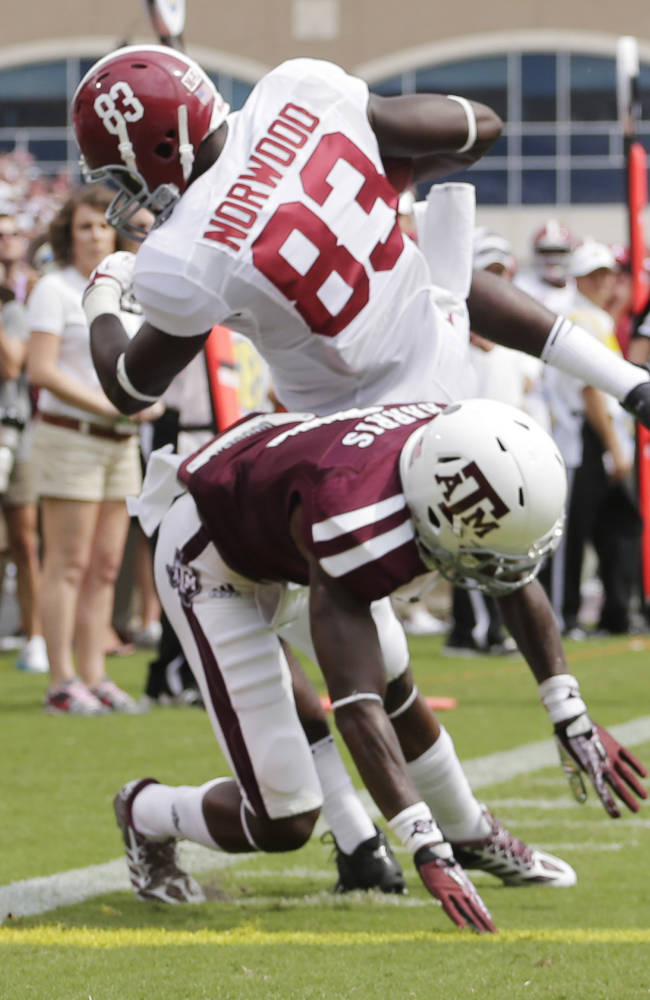 Alabama wide receiver Kevin Norwood (83) comes down with a 22-yard touchdown pass as Texas A&M defensive back De'Vante Harris (1) defends during the first quarter of an NCAA college football game Saturday, Sept. 14, 2013 in College Station, Texas