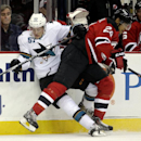 San Jose Sharks center Tommy Wingels, left, is slammed to the boards by New Jersey Devils defenseman Bryce Salvador during the first period of an NHL hockey game, Saturday, Oct. 18, 2014, in Newark, N.J The Associated Press
