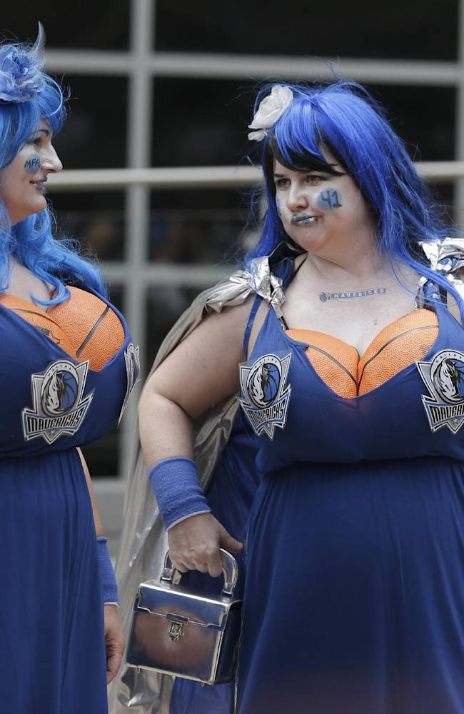 Darci Crouch, left, and Tina Parker wait in costumes to enter the arena for Game 3 of a first-round NBA basketball playoff series between the San Antonio Spurs and Dallas Mavericks in Dallas, Saturday, April 26, 2014
