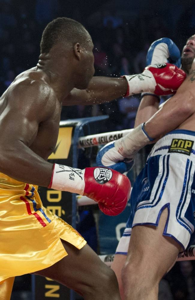 Adonis Stevenson, left, of Canada, connects with a left to Tony Bellew, of England, in their WBC light heavyweight title fight in Quebec City early Sunday, Dec. 1, 2013. Stevenson won the fight